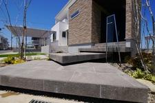 浮かぶアプローチ 石目タイルの玄関とテラス